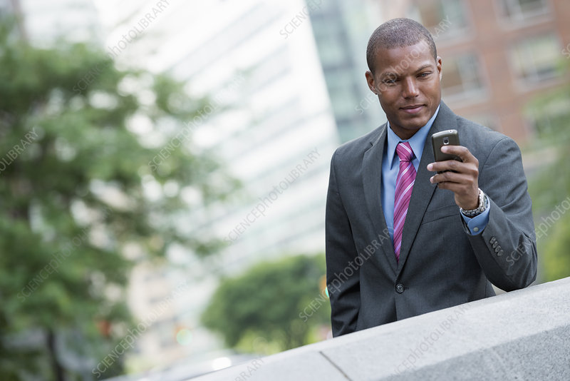 Man in a shirt and tie on a smart phone