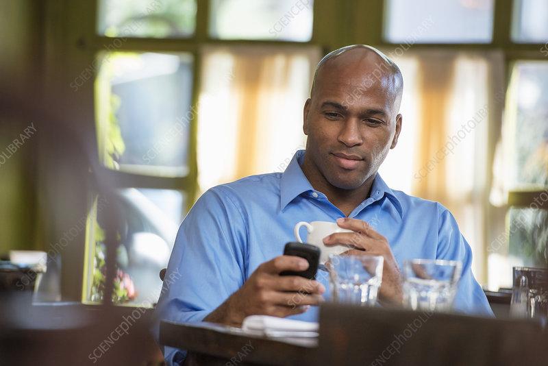 Businessman sitting checking his phone