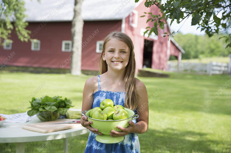 Girl carrying bowl of green apples