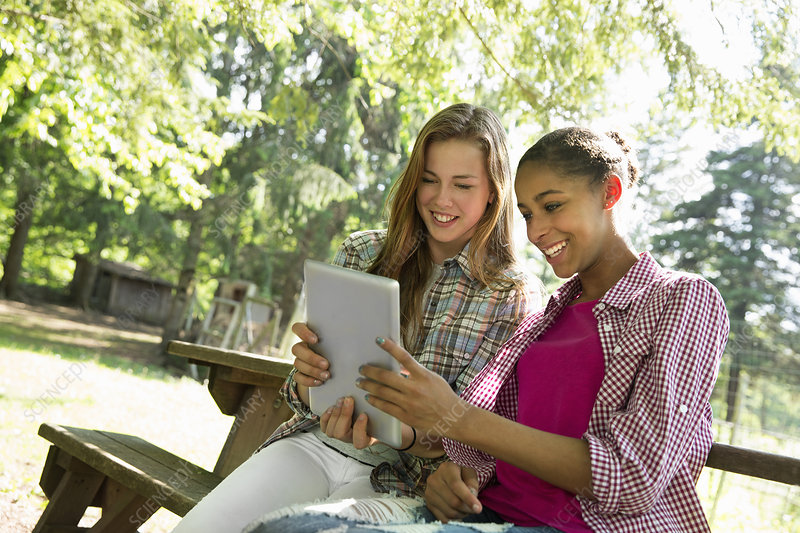 Two girls using a digital tablet outdoors