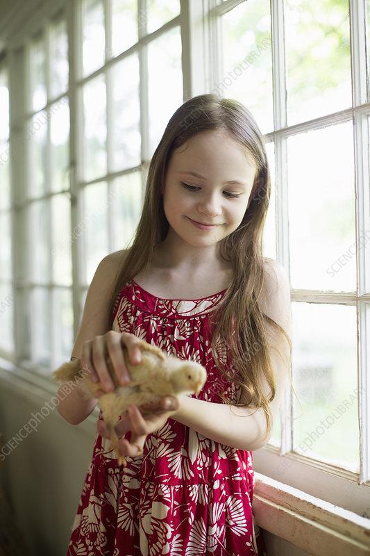 Girl in sundress holding fluffy chick