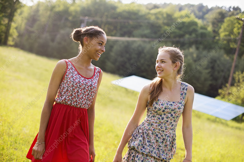Two girls on farm beside a solar panel