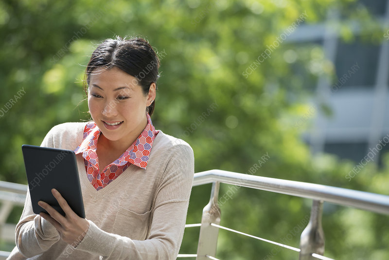 Woman using digital tablet in the park