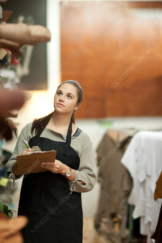 Young woman working in leather stockroom
