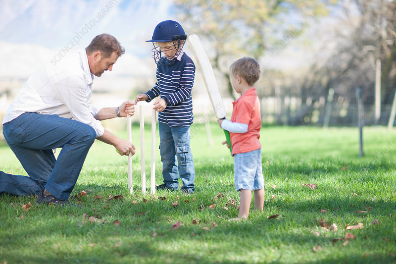 Father and sons preparing cricket stumps