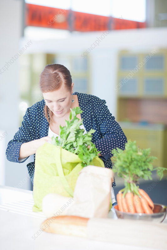 Young woman looking in grocery bags