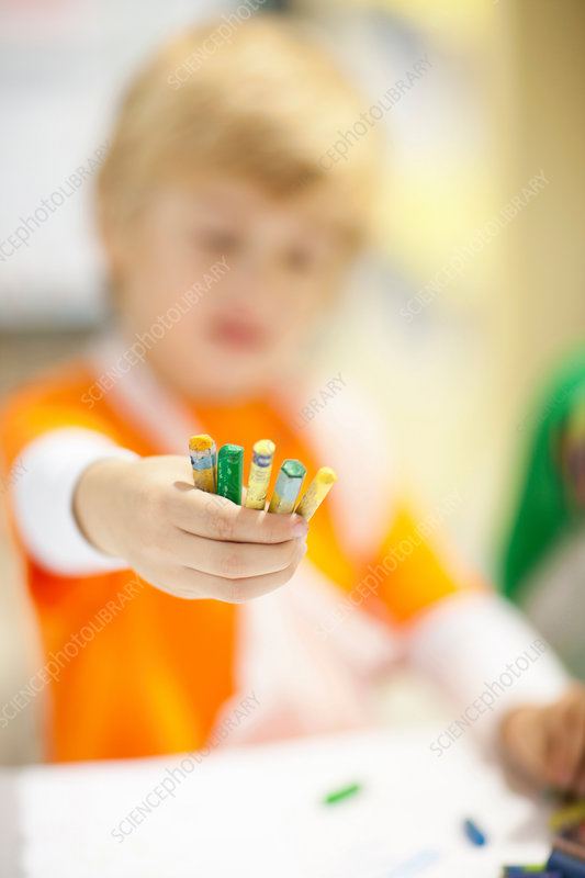 Boy holding out crayons