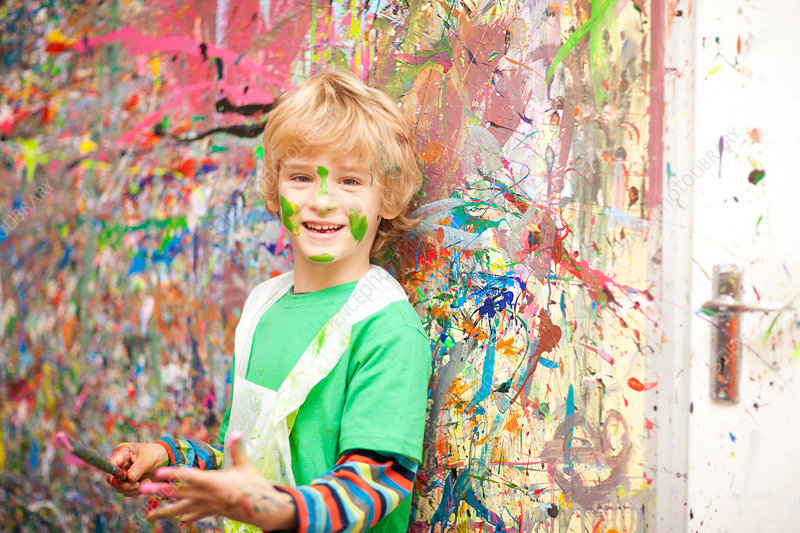 Boy in front of paint-splattered wall