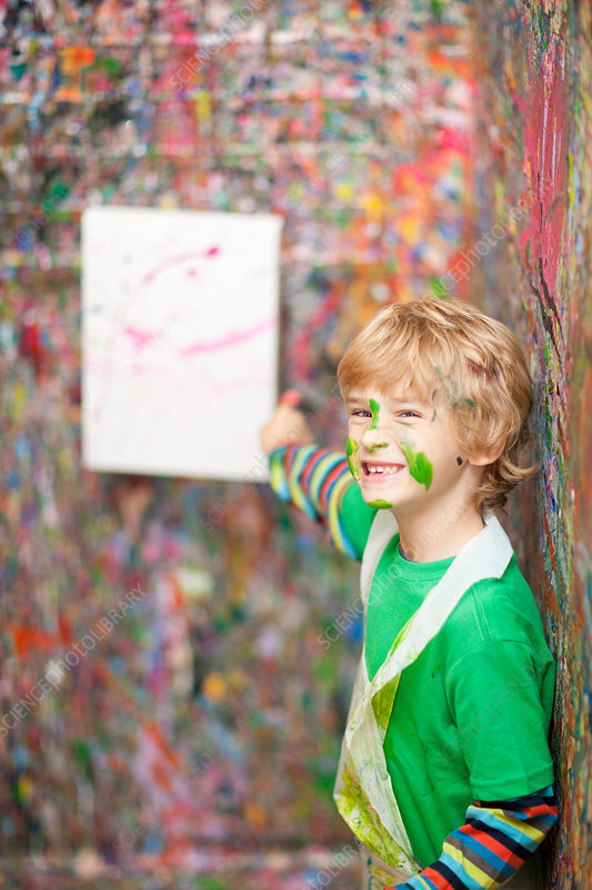Boy pointing to paint-splattered wall