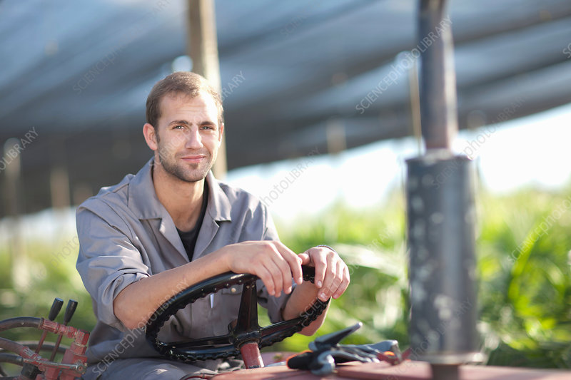 Young man on vehicle in plant nursery