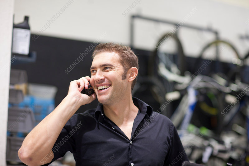 Mid adult man on cell phone in bike shop