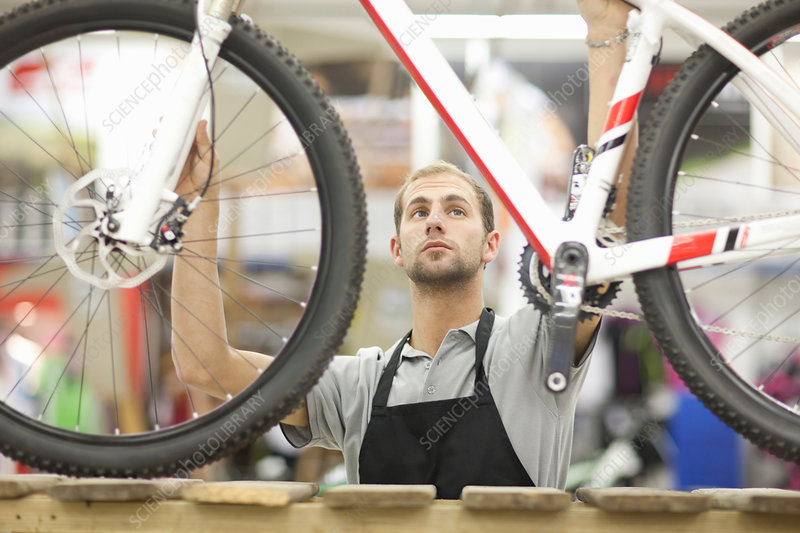 Young man holding bicycle in repair shop