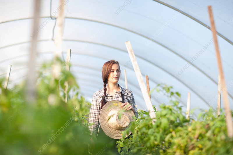 Young woman in vegetable greenhouse