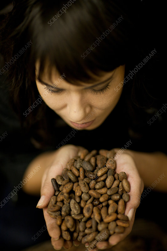 Woman holding handful of cocoa beans
