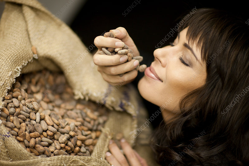 Woman smelling cocoa beans
