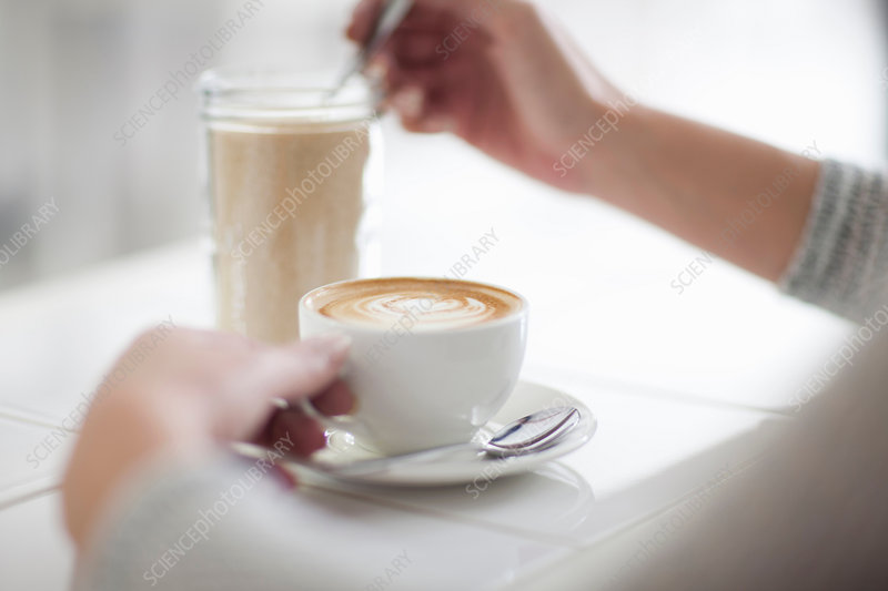 Woman in cafe with coffee cup, close up