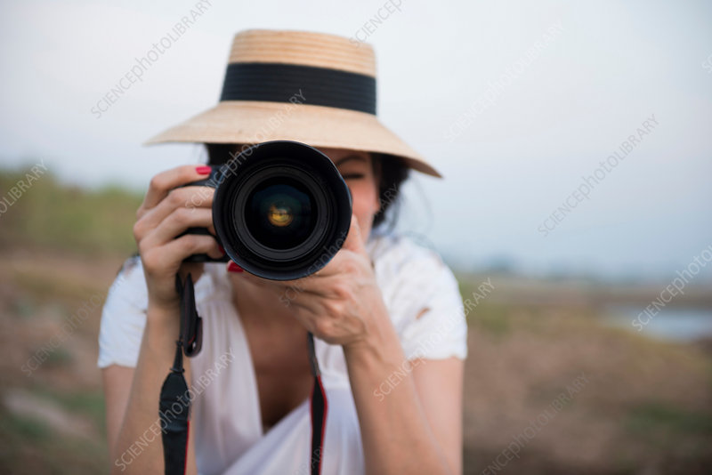 Woman wearing hat taking photograph
