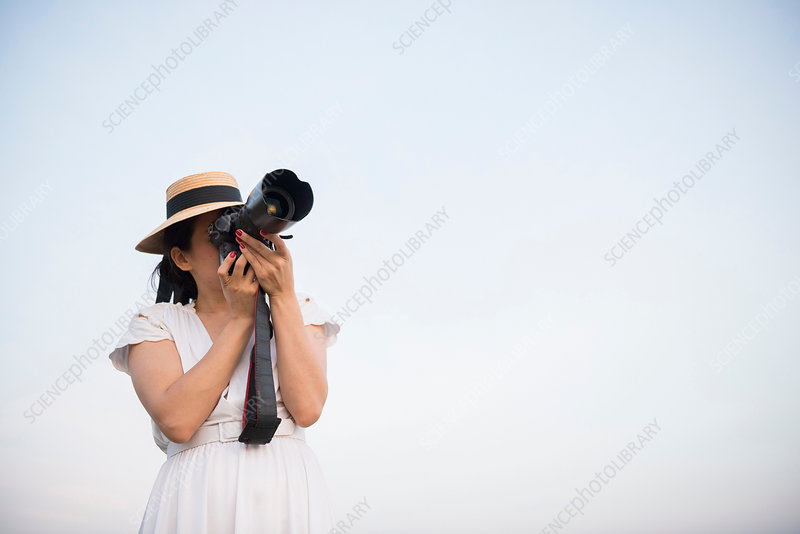 Woman taking photograph against clear sky