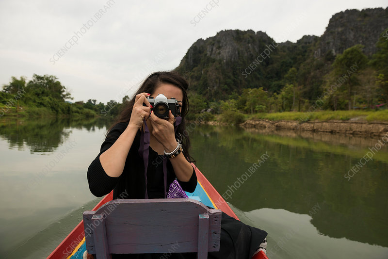 Woman taking photograph on boat, Laos