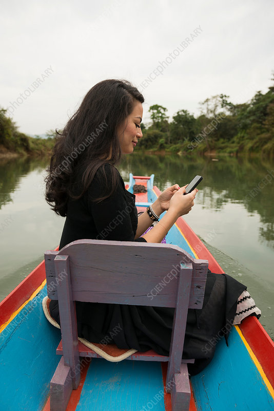 Woman with mobile phone on boat , Laos