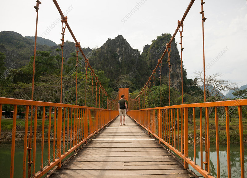 Man on bridge over river, Laos