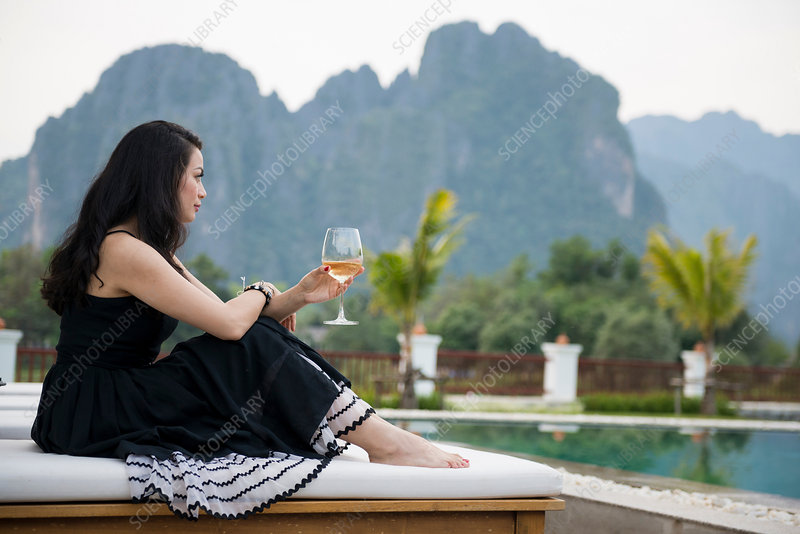 Woman with wine glass by poolside, Laos