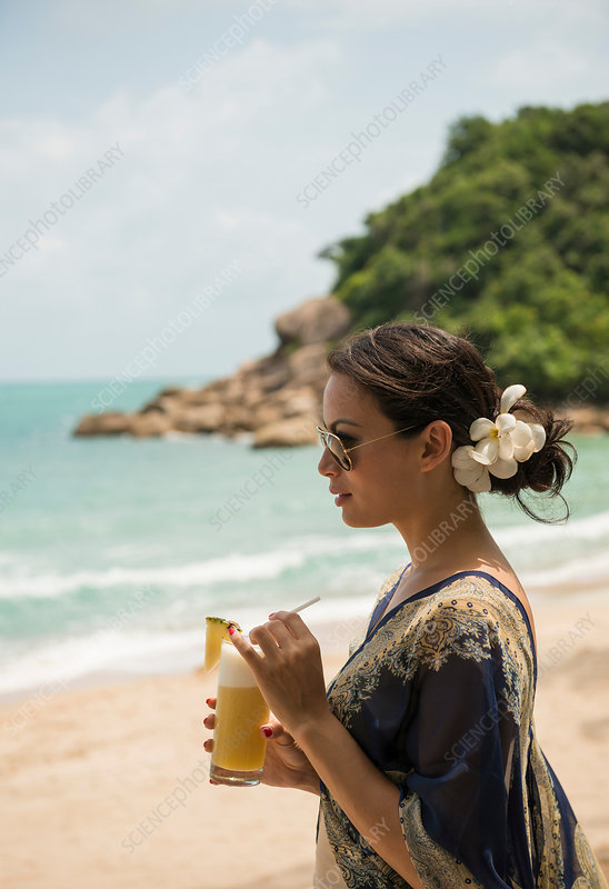 Woman with drink on beach, Thailand