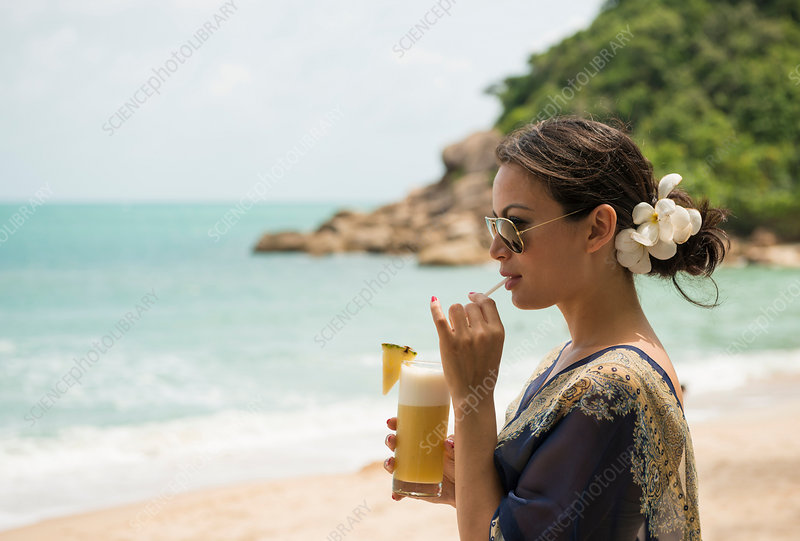 Woman drinking on beach, Thailand