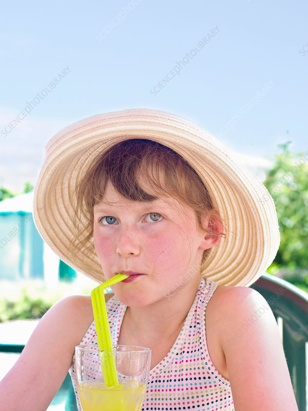 Girl wearing sunhat drinking soft drink