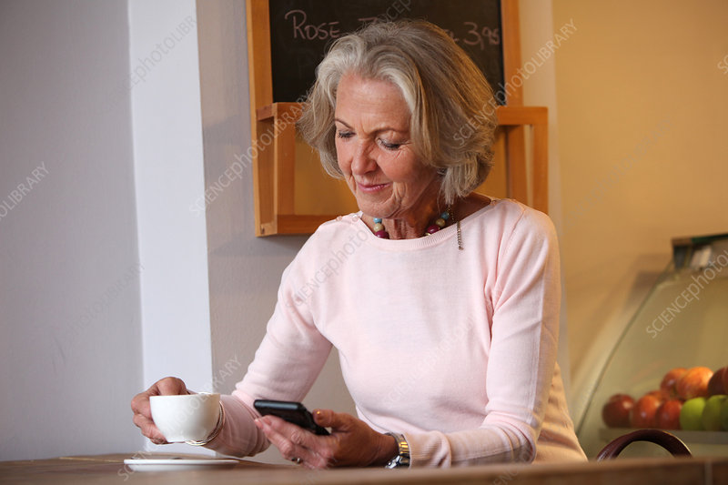 Woman holding coffee cup and mobile phone