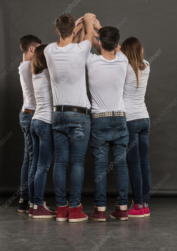 Five teenagers in huddle with arms raised