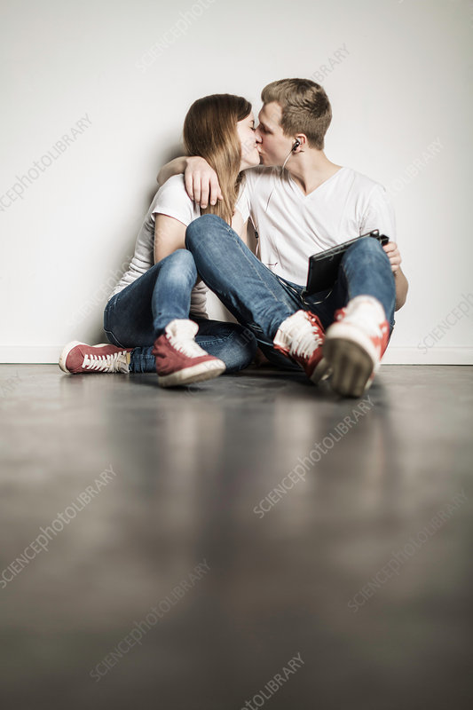 Teenage couple sitting on floor kissing