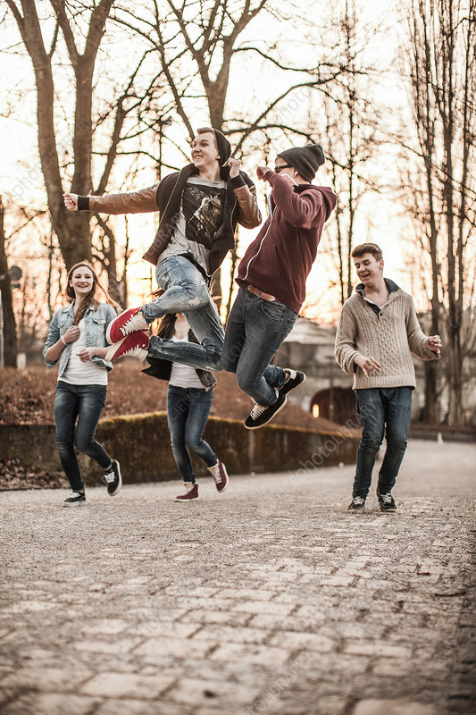 Five teenagers jumping in park