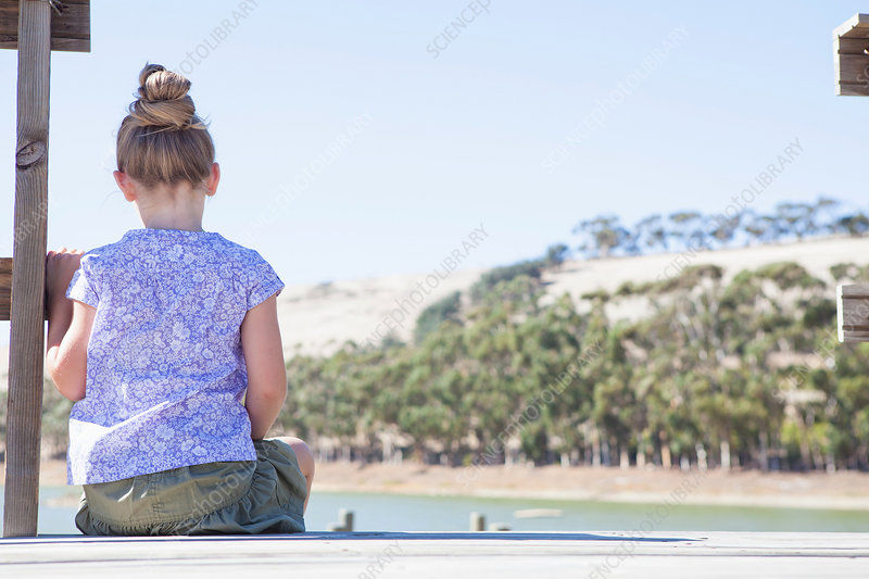 Girl sitting on pier, rear view