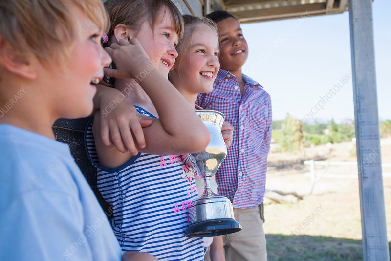Four children with trophy, looking away