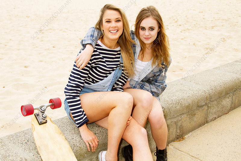 Girlfriends sitting on wall at beach