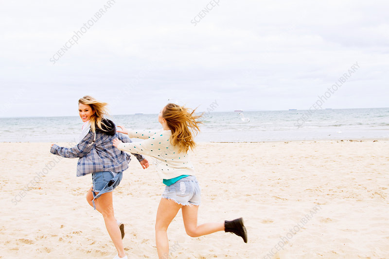 Girlfriends playing chase on the beach