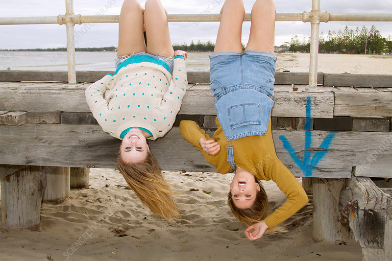 Girlfriends hanging upside down from pier