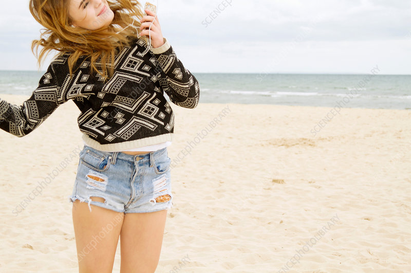 Young woman dancing on beach