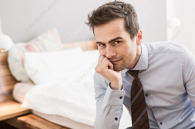 Man wearing shirt and tie sitting on bed