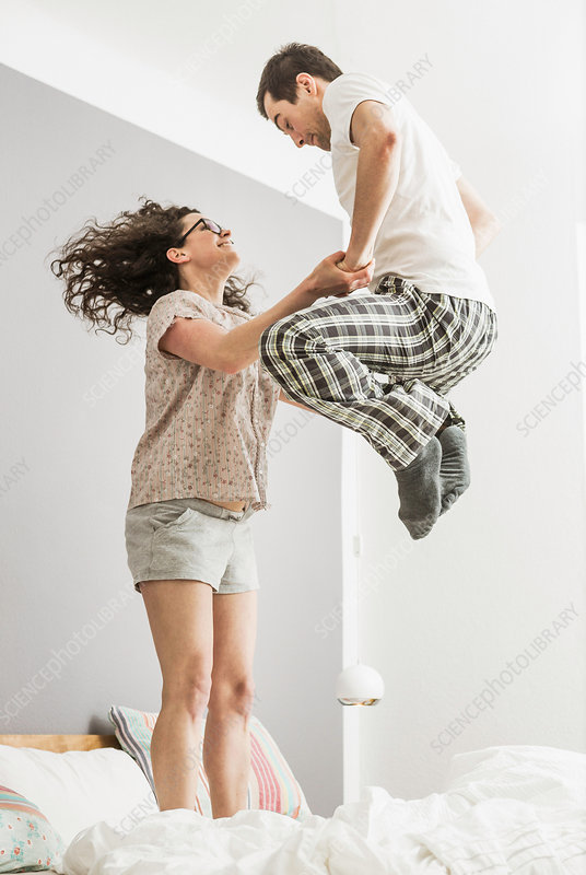 Couple wearing pyjamas jumping on bed