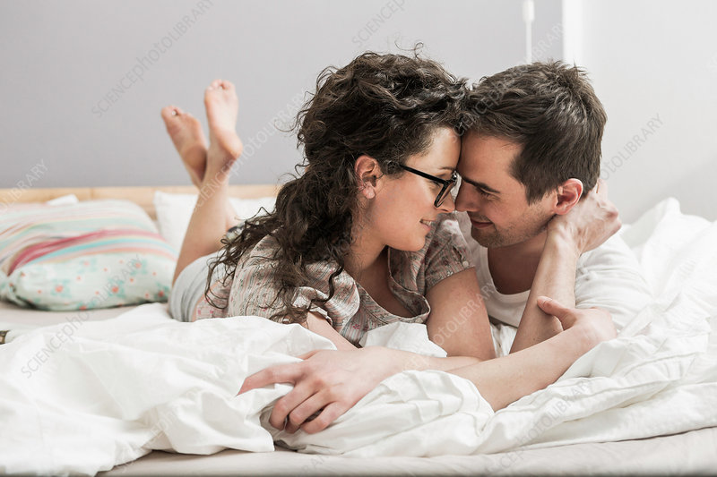 Couple lying on bed, face to face