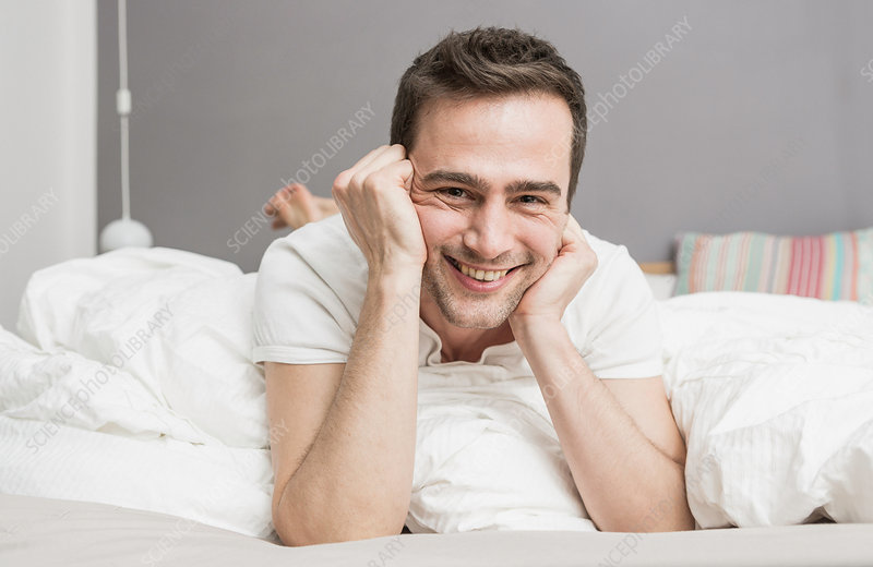 Mid adult man lying on front on bed