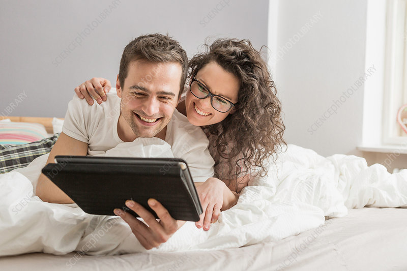 Couple lying on bed using digital tablet