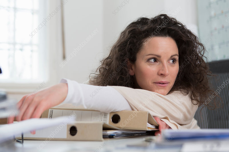 Woman sitting at desk leaning on folders
