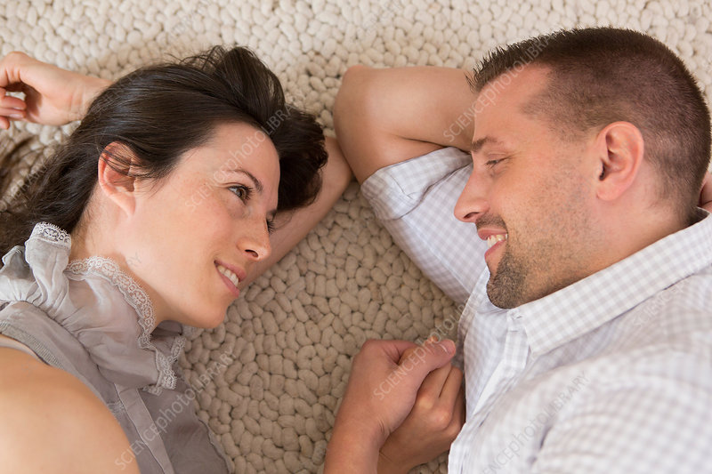 Couple lying on floor face to face