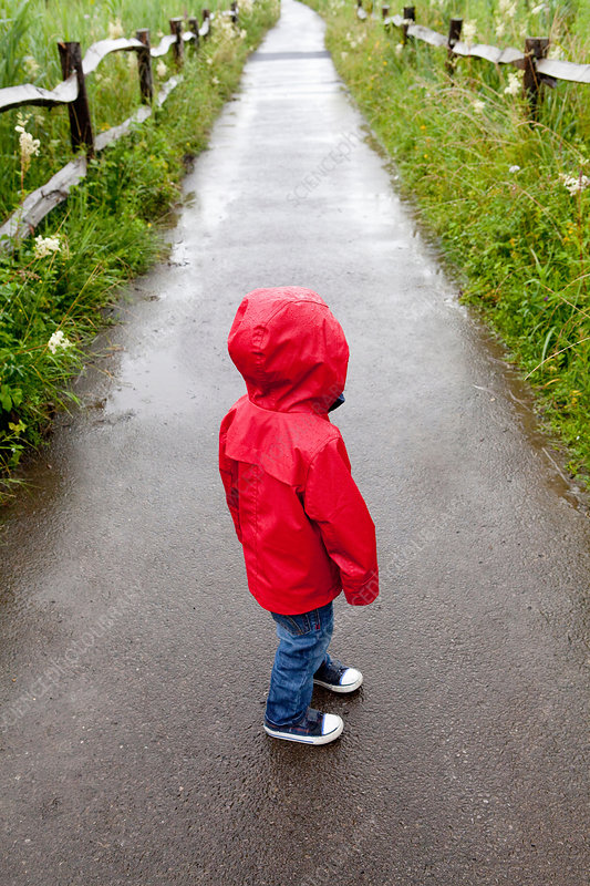 Toddler standing on path in red raincoat