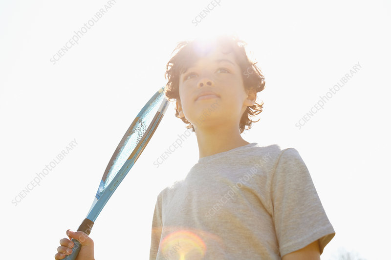 Boy holding up tennis racket