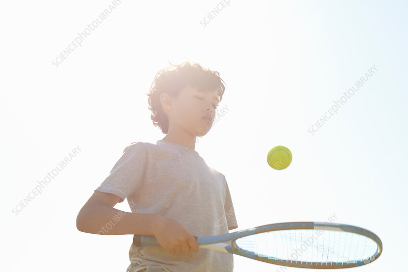 Boy bouncing ball on tennis racket