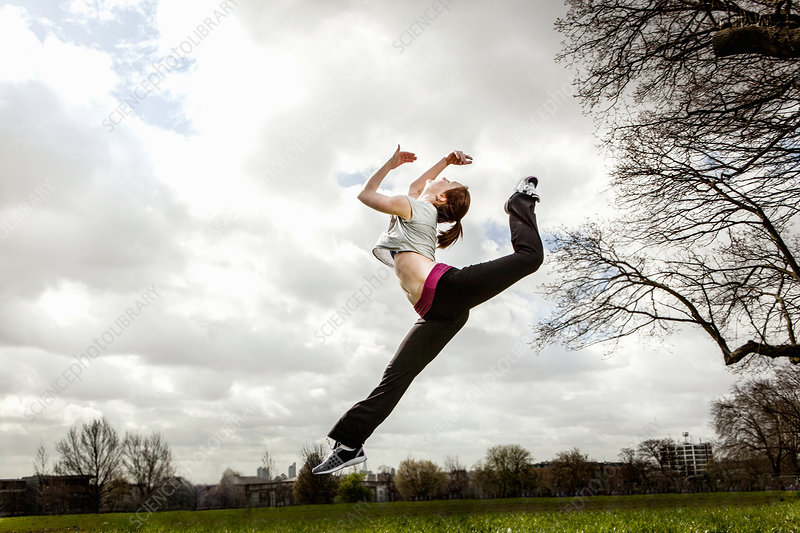 Woman jumping in mid air with bent leg